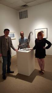 Dakota Carlson, Dr. Merrill Cole, and Alyson Eagan stand proudly around a metal rooster after reading at the final Boiler Room Reading Series of the school year.